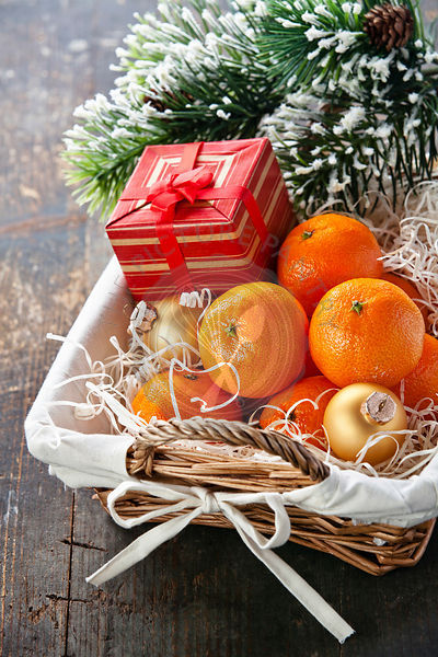 Mandarins in basket with Gift and Christmas tree branch