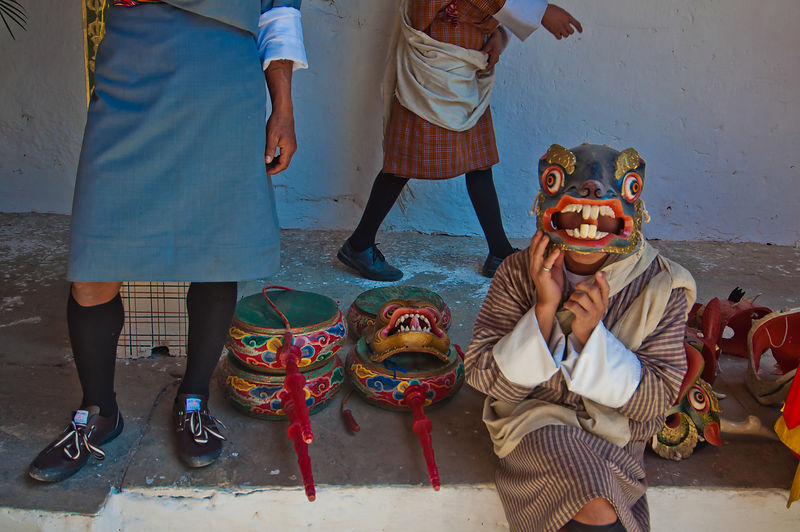 One of the attendees of the Thimphu festival tries on a mask while others walk past him.