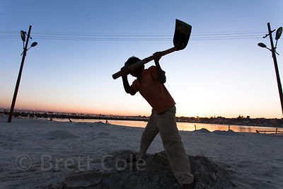 A boy digs a pit in the beach at the 2013 Kumbh Mela, Allahabad, India.