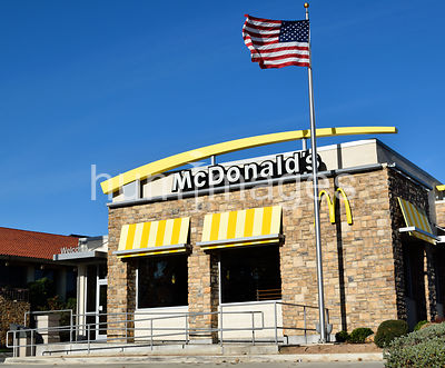 McDonalds restaurant and American flag on windy day - Texas