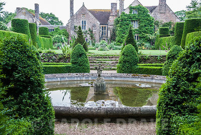 Circular pond surrounded by clipped yew below the manor house at Cothay in Somerset