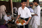 India - Srinagar - A waiter takes tramis (plates) from the Wazas (traditional Kashmiri cooks) to serve to guests at  a Wazwan...