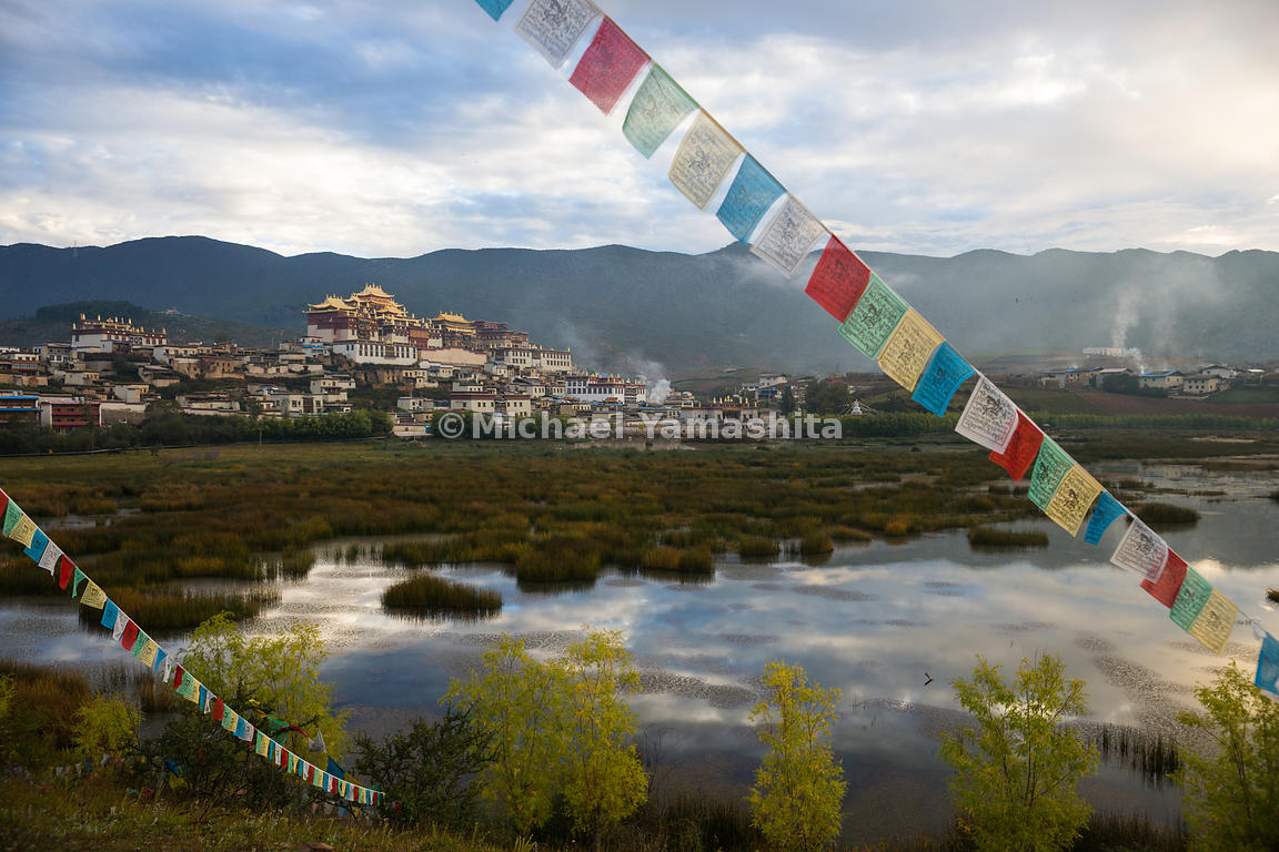 "Tibetan prayer flags frame Songzanlin Monastery, the largest Tibetan Buddhist monastery in Yunnan. ""With its gilded roofs, it..."