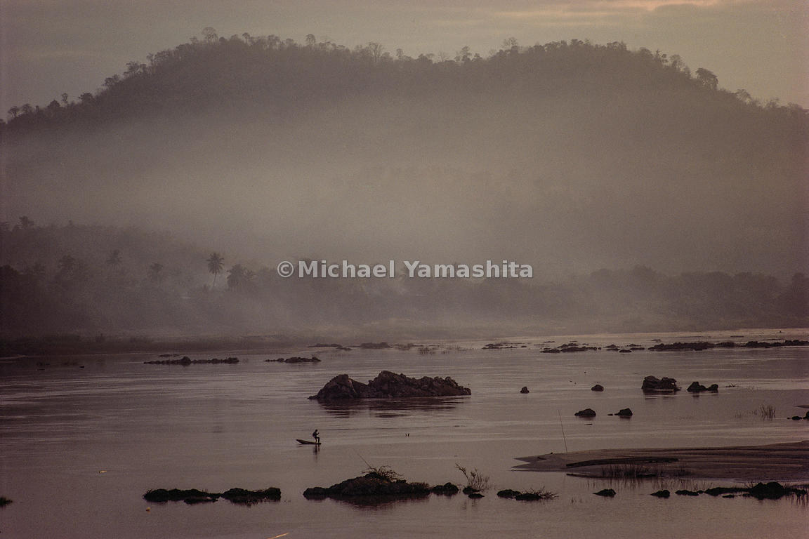 Guided by first light, a fisherman, plies the rock-studded Mekong on the Laos-Thailand border.