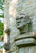 Detail of carved heads on stone dovecot. Westonbury Mill Water Garden, Pembridge, Herefordshire, UK