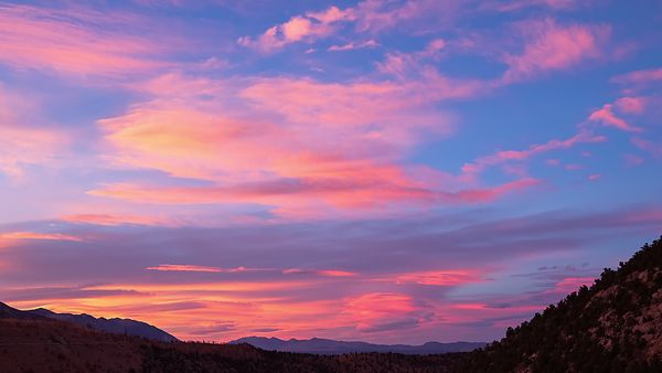 Medium Shot: Vibrant Sunset Over Mountain Ranges & Lenticulars'