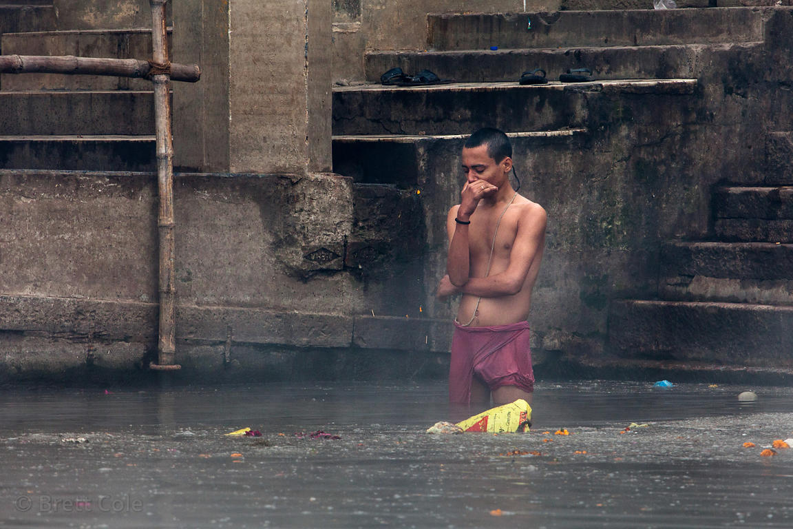 A man bathes in foul water in the Ganges River near Scindhia Ghat, Varanasi, India. Trash is routinely dumped in the river.