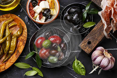 Italian snacks food with Olives, Feta cheese with dried tomatoes, Ham, Garlic, Basil and Pepperoni pepper on dark marble background close-up