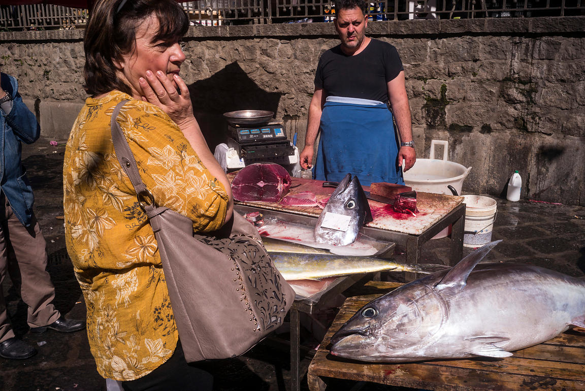 Stallholders at the Mercato della Pescheria Market sell tuna to a woman customer