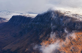 A snow and cloud covered summit of Beinn A Mhuinidh above Loch Maree in the Scottish Highlands, Scotland, UK.