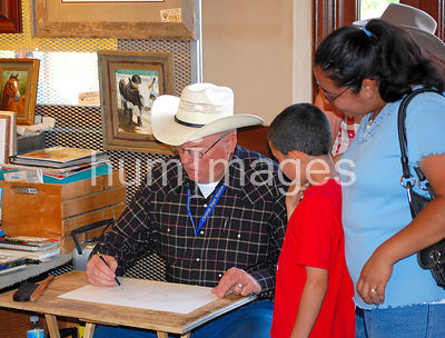 Little boy and mother look on as a cowboy artist draws a picture