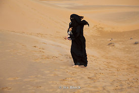 A local woman with a veil called niqāb and robe-like dress called abaya walking at Empty Quarter desert.