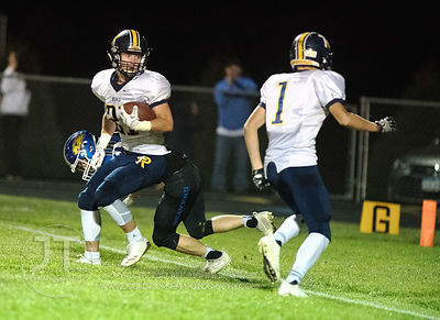 Iowa City Regina's Jacob Phillips (21) spin moves his way into the endzone against Wilton during the second half of play in W...