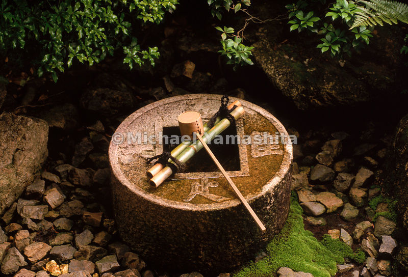 A hishaku, bamboo ladle, sits on an ablution basin inset in a stone in the Ryoanji rock garden in Kyoto. Ritual cleanliness i...