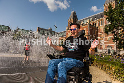 Couple using power wheelchairs around a fountain in an historic garden