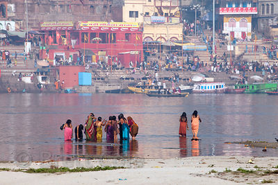 Hindu women pilgrims in saris bathe in the Ganges River, Varanasi, India.