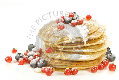 Small pancakes topped with red currants and bilberries on white background