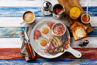 Full English breakfast in white pan with fried eggs, sausages, bacon, beans, toasts, orange fresh and coffee on wooden background