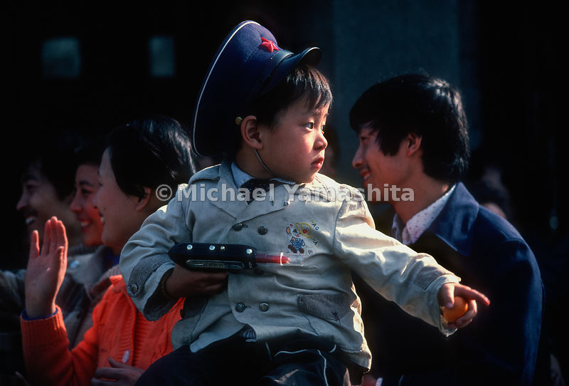 A young boy holds a toy gun. Zhenjiang, Jiaoshan, China