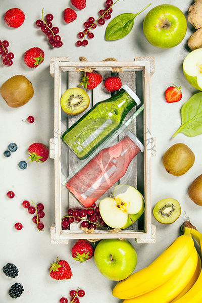 Green and red fresh juices or smoothies with fruit, greens, vegetables on grey background, top view, selective focus. Detox, ...