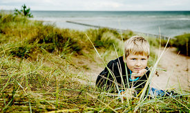 Younger Nordic boy in sand dunes