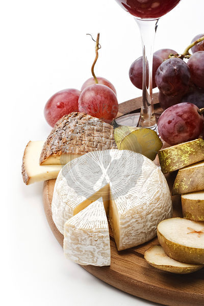 Wineglass with red wine and assortment of cheese and fruits on white background