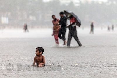 A boy plays in the Arabian Sea in monsoon rains, Juhu Beach, Mumbai, India.