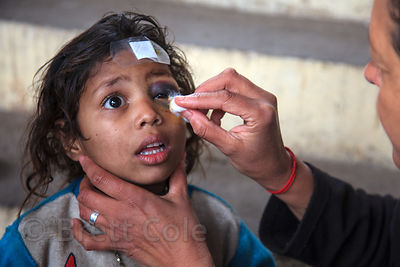 "A nurse from the French NGO Agir pour Benares tends to a girl with a ""black-eye"" at a free health clinic at the Burning Ghats..."