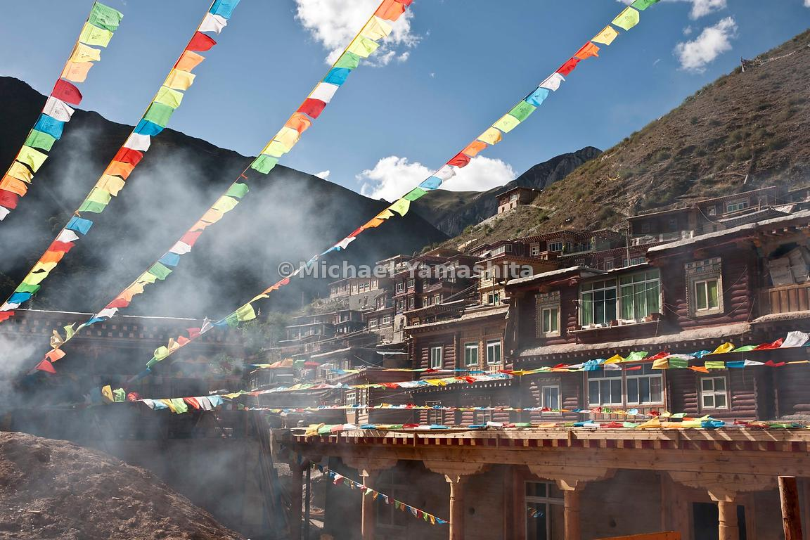 Prayer flags in primary colors symbolizing the five elements offer protection for the newly constructed dormitories at Dege G...