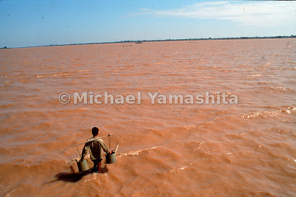 A farmer takes advantage of the flood swollen Mekong outside Phnom Penh, Cambodia to fill his irrigation buckets. The river b...