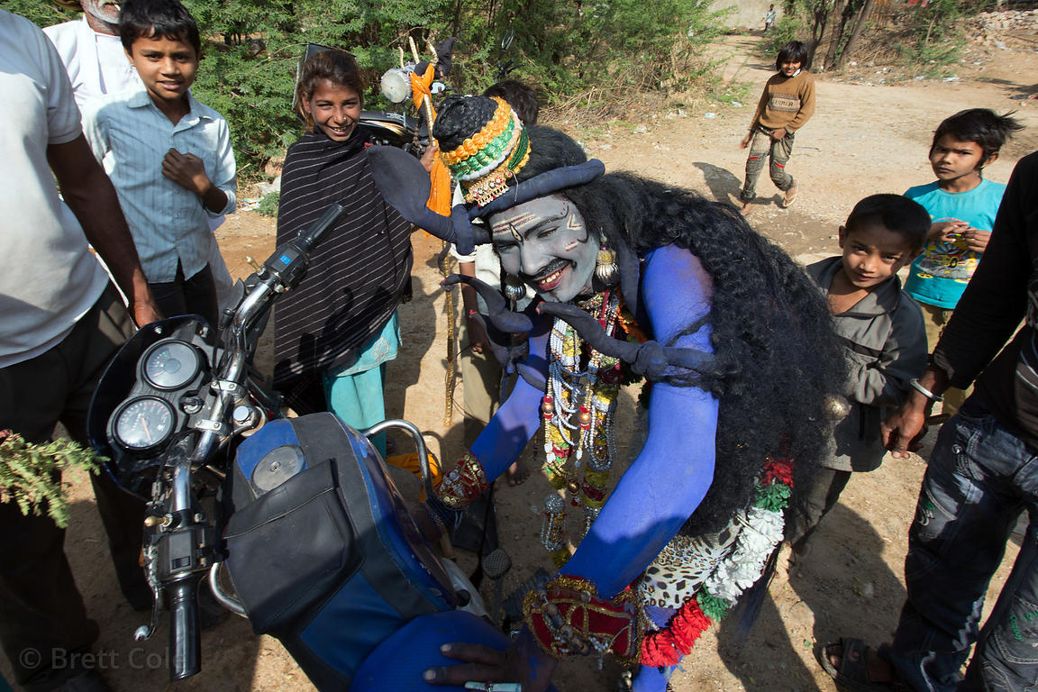 A man dressed as Shiva works on his motorcycle before heading to Pushkar to have his picture taken by tourists on Mahashivara...