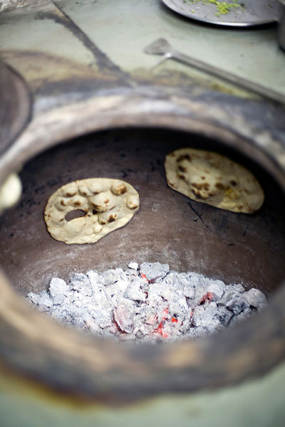 India - Delhi - Chapati breads in the tandoor oven at the Village Restaurant