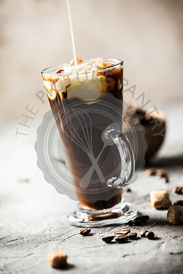 Ice coffee in a tall glass with cream poured over and coffee bea