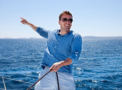 Croatia, Zadar, Young man pointing from sailboat, smiling