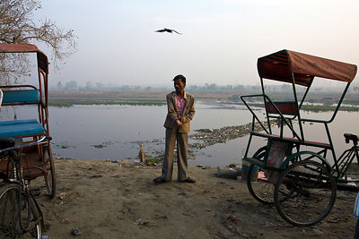 India - New Delhi - A homeless cycle rickshaw driver dresses at a parking lot next to the Yamuna River where he sleeps