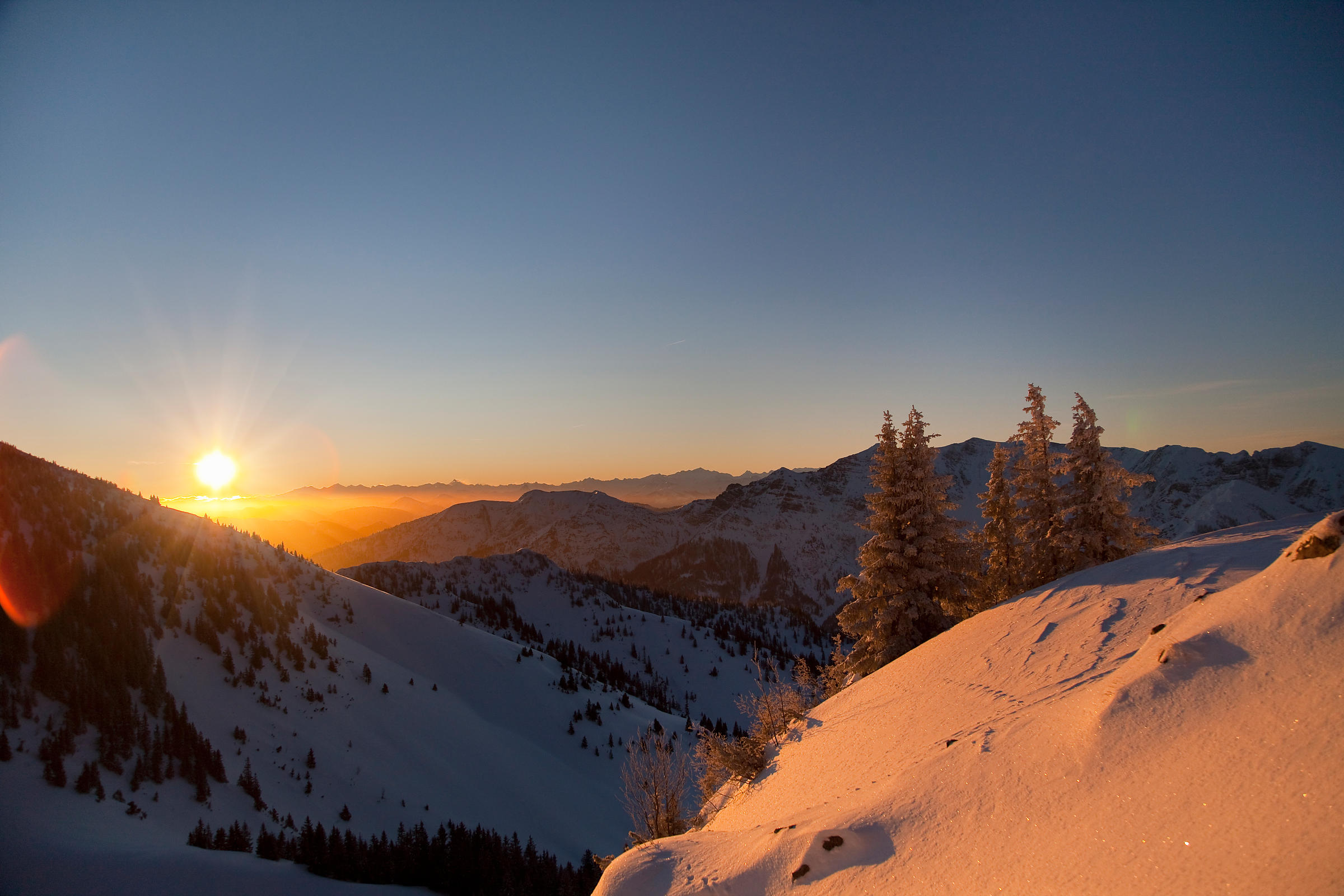 Sun setting over snowy landscape