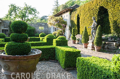 Box parterre with Casita beyond and Italian marble statue of youth against the yew hedge. Iford Manor, Bradford-on-Avon, Wilt...