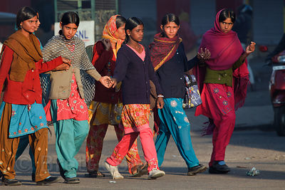 A group of women walk on a main throroughfare in Jodhpur at sunrise, Rajasthan, India