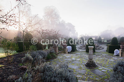 The Fountain Court on a winter's morning at Mapperton, Dorset, featuring crab apples, lavender, clipped yew and decorative ur...