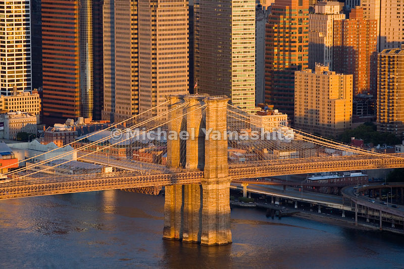 The solidity of the Brooklyn Bridge's towers makes its suspension cables seem almost delicate by comparison.  Manhattan, New ...
