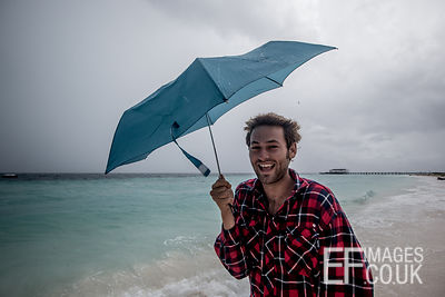 Man With An Umbrella On A Stormy Beach