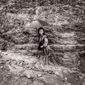 Hmong Girl with Umbrella Next to Mud Hill