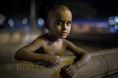 A small boy poses for a portrait at night, on a busy street with no parents anywhere in sight. He called me over and inisted ...