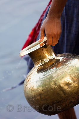 A woman carries a water pot along the Hooghly River during the Durga Puja festival in Kolkata, India.