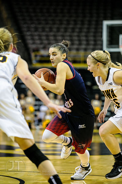 Robert Morris' Megan Smith (22) drives between Iowa's Kali Peschel (25) and Whitney Jennings (15) during the first half of pl...