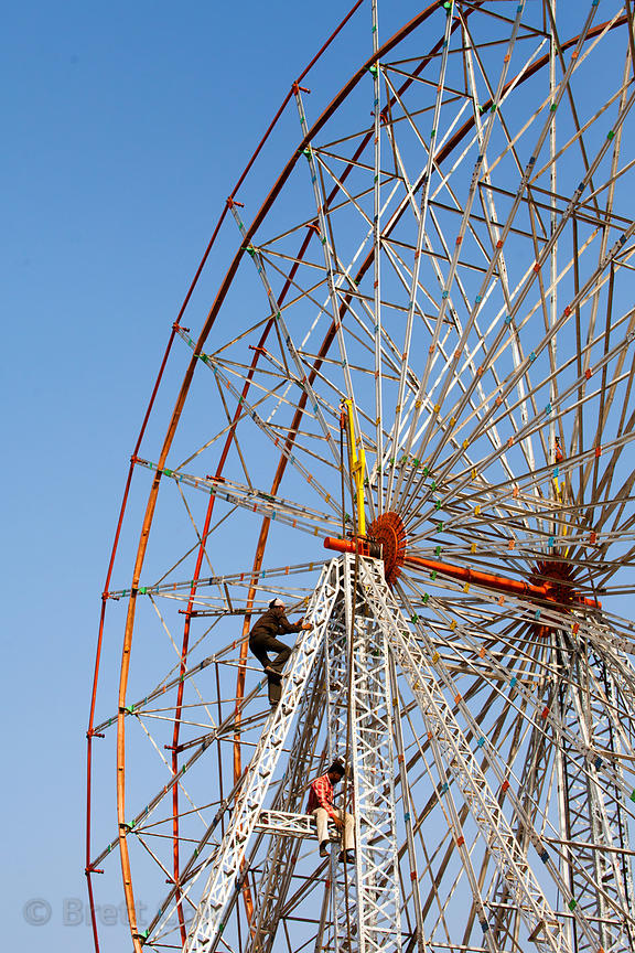 Workers make adjustments to a ferris wheel at a carnival, Pushkar, Rajasthan, India.
