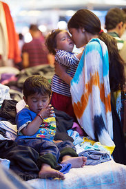 A mother embraces her toddler at a clothing stall at the main market in Kullu, India