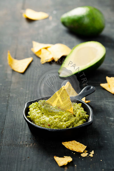 Mexican nachos chips with homemade fresh guacomole sauce over old  background. With space for text