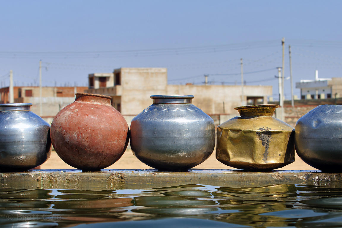 Metal and clay water pots at a water trough, Pushkar, Rajasthan, India