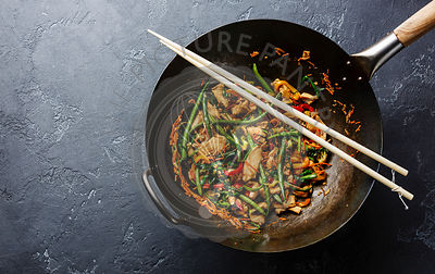 Stir fry chicken with sweet peppers and green beans in wok pan on dark stone background copy space